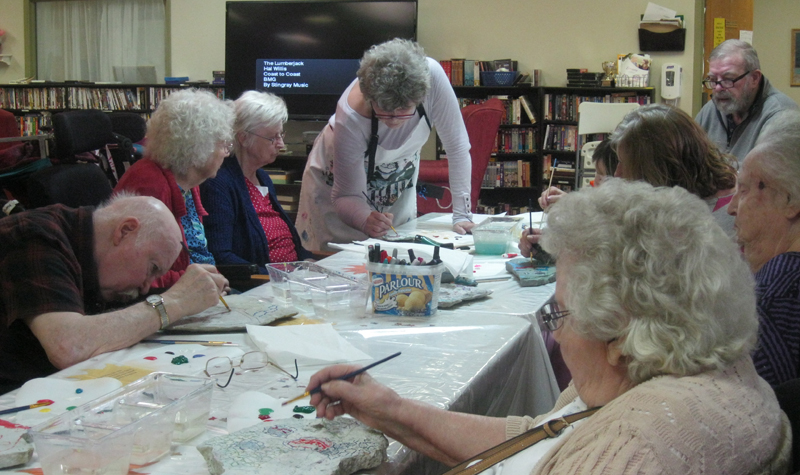 residents are sitting at a table painting