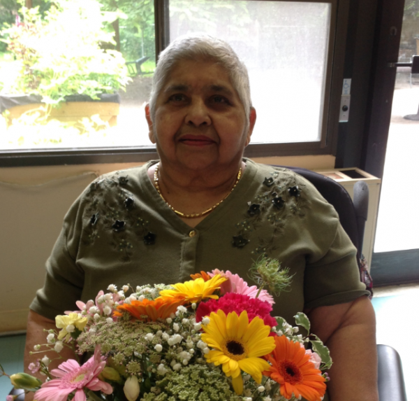 A woman sits in a wheelchair with flowers in her lap