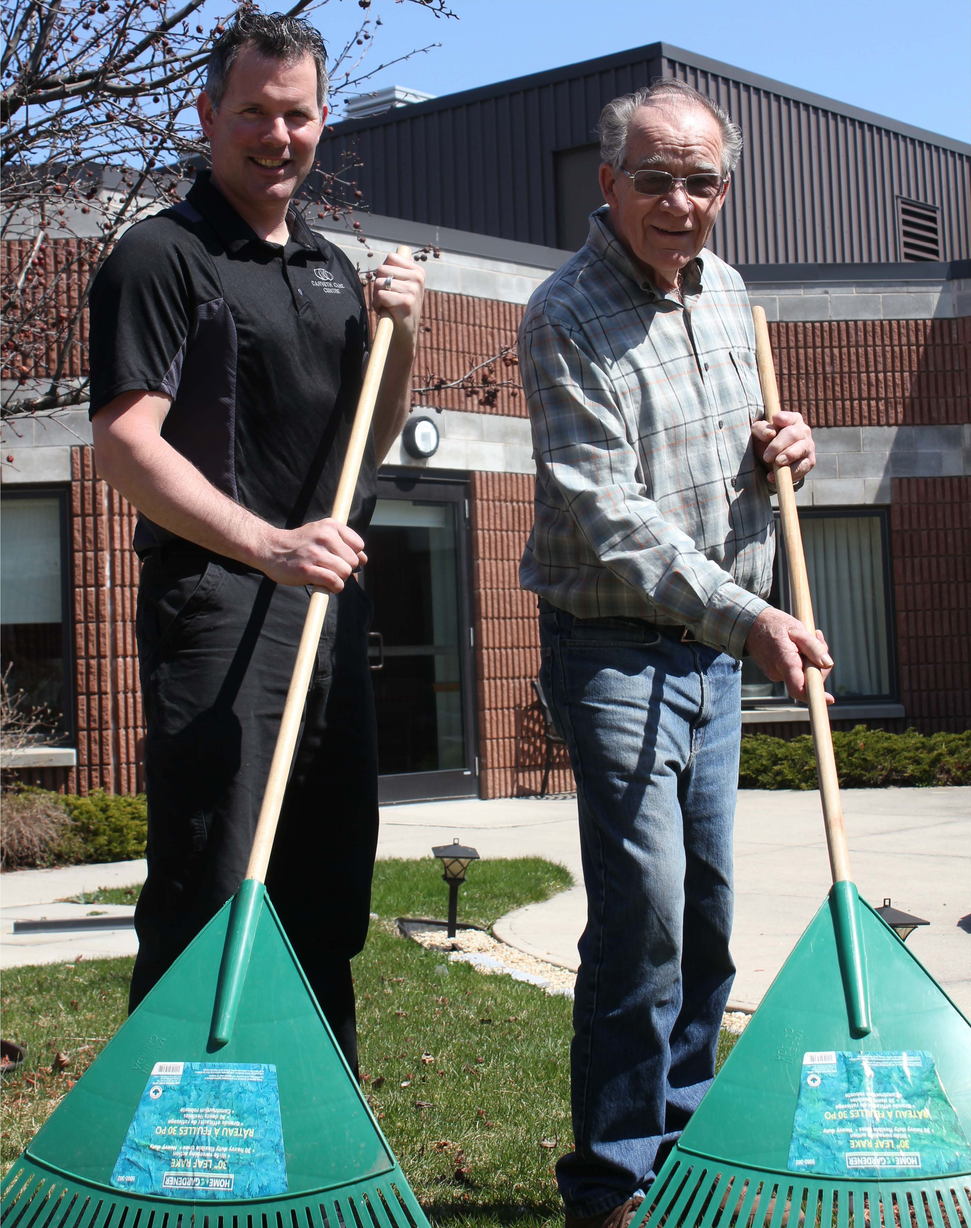 Environmental services manager Tim Keyes and resident Gord Palmer stand side by side raking leaves in front of Carveth Care Centre, with smiles on their faces.