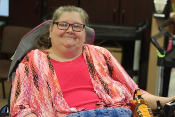 Carol Gloster sits in a wheelchair, smiling for the camera