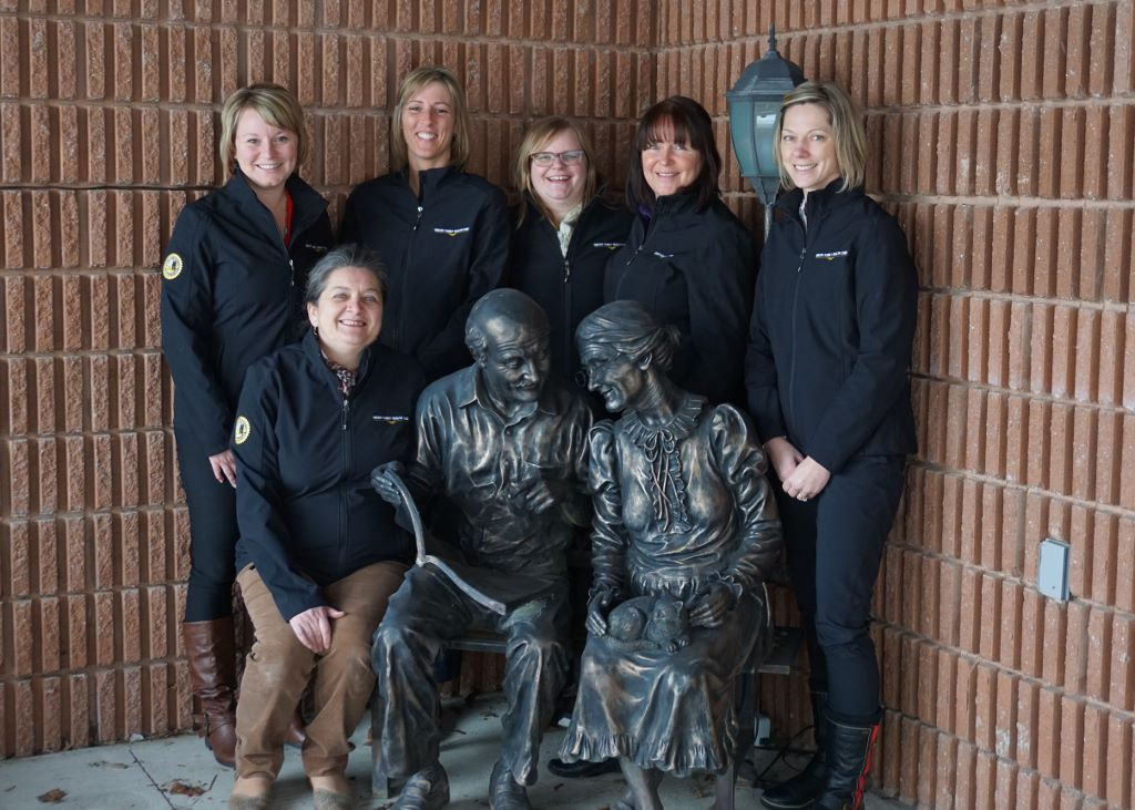 Carveth Care Centre's Activation Team pose together for a photo outside the long-term care home, along with two statues