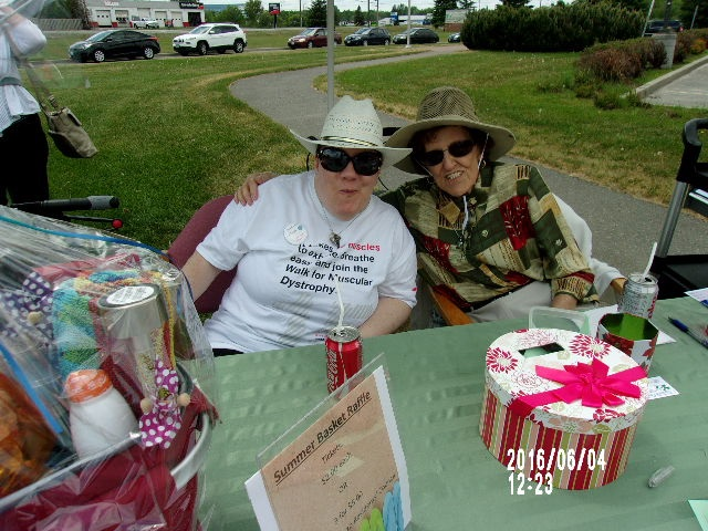 Corrine Mattinen and Ann Marie Paquette, residents' council members, man the council's raffle draw, sitting at a table and posing for the camera with the raffle prize beside them