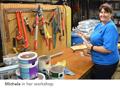 Michele stands in front of her work bench with paint cans on it and a tool board behind it
