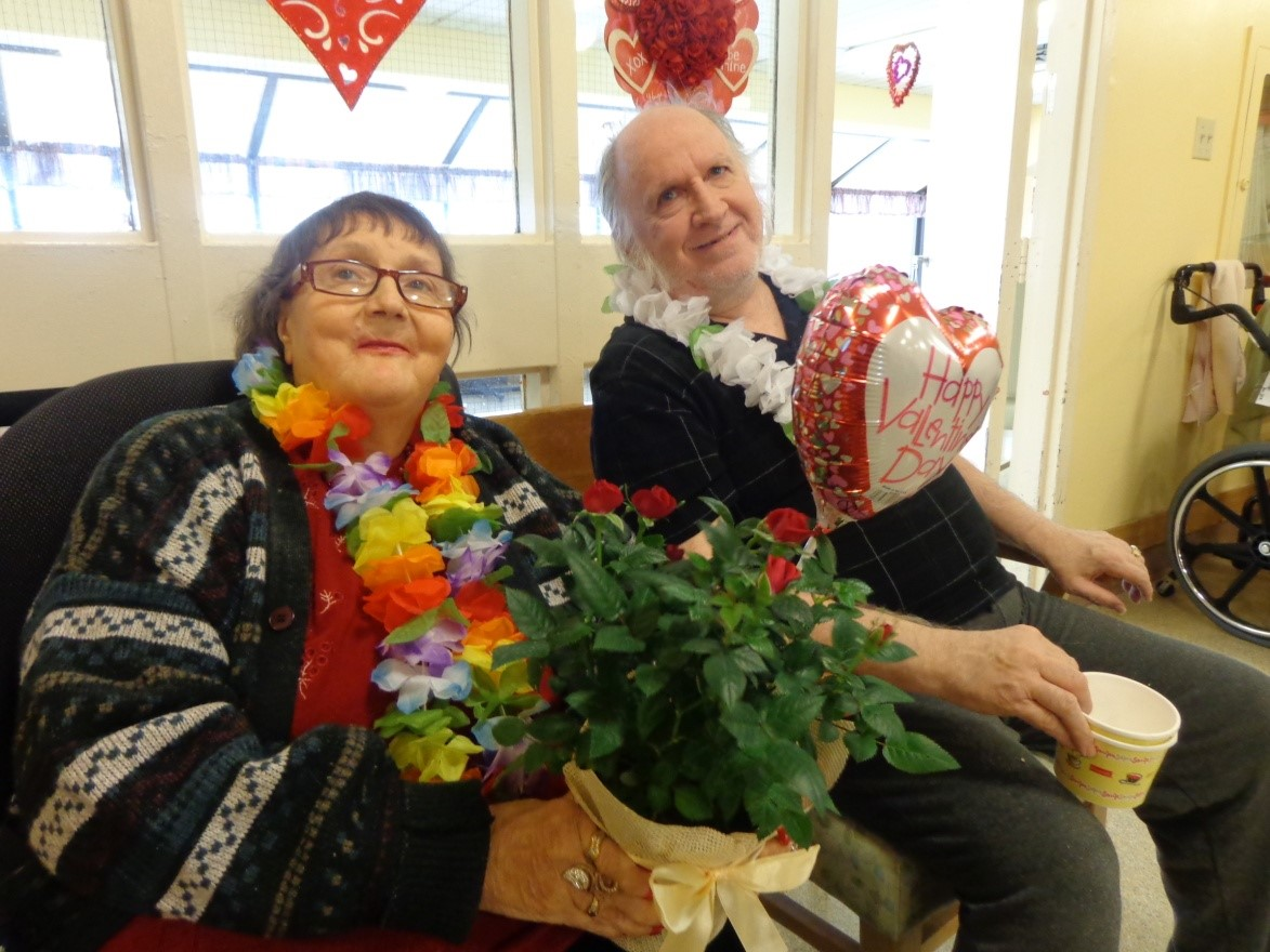 Kristina and Allan sit together smiling. She is holding flowers and there are Valentine's balloons around them.