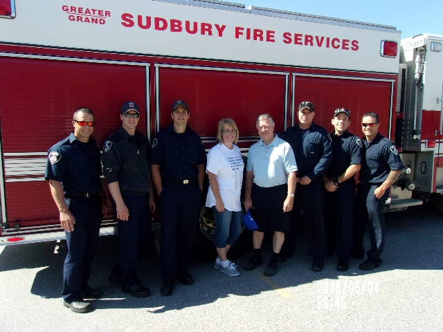 Liane Pelissier and Robert Kirwan, ward councilor, are standing in front of a fire truck, smiling with a group of local firefighters who came out to support the event