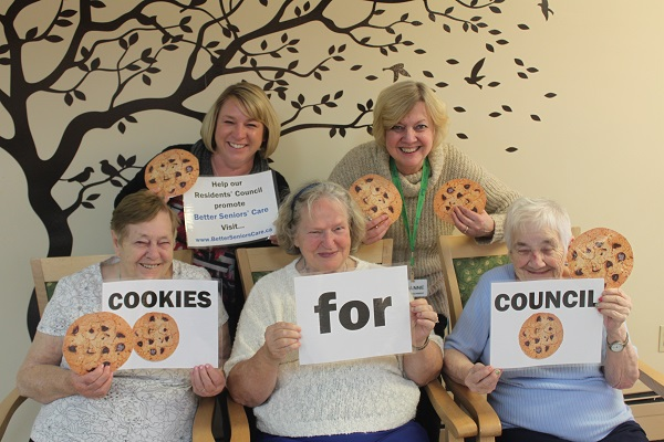 residents and staff hold up Cookies for Council signs to promote their baking fundraising