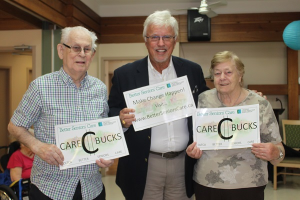 Two residents stand on either side of MPP Rick Nicholls, holding signs for Better Seniors Care