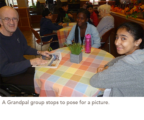 A resident sits at a table with two students, smiling for the camera