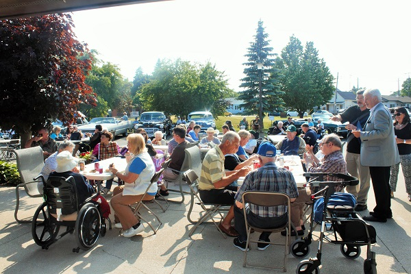 a group of residents and family members are seated at picnic tables, enjoying bbq outdoors on a sunny day