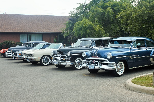 A line of classic cars sit in Meadow Park's parking lot