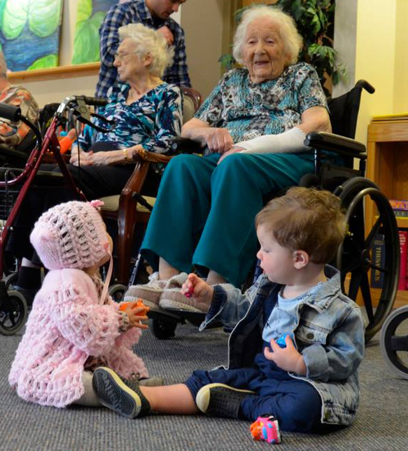 A resident in a wheelchair smiles at two toddlers on the floor in front of her who are playing with their chocolate eggs
