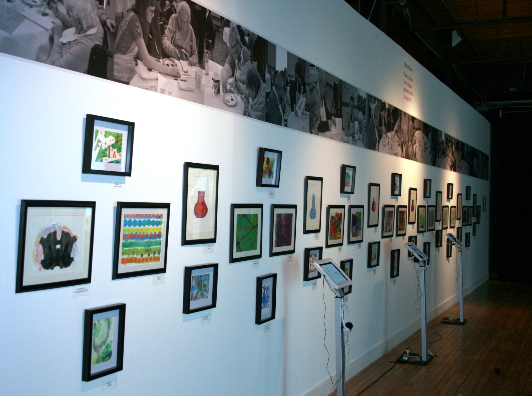 A wall of art is displayed in the hallway of Trinity Village