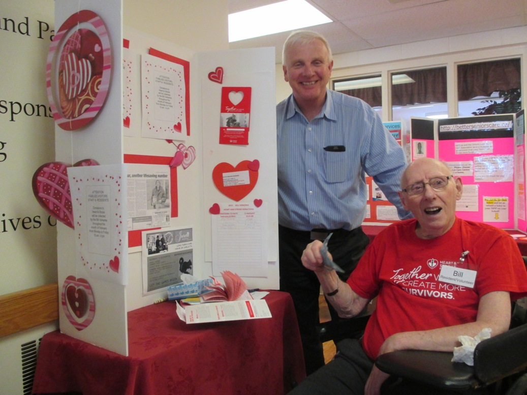 Bill sits in a chair in front of his display to bring attention to his heart and stroke fundraiser. David Jarlette, president of Jarlette, stands behind him after having just donated funds.