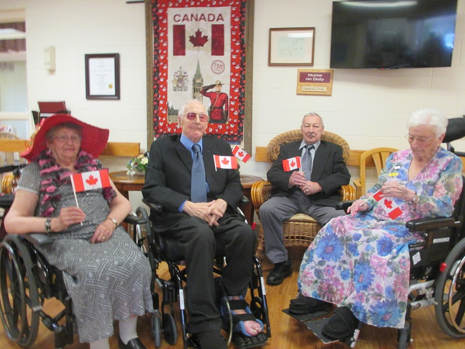 Two women and two men sit in wheelchairs smiling and holding Canadian flags