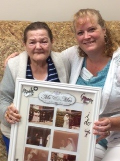 Two woman - Susan and Dale - hold up a picture frame with photos from Susan's wedding day