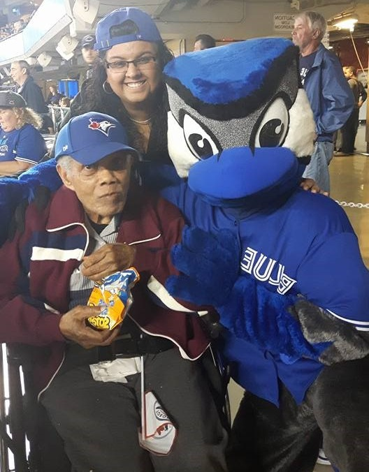 A man sits in a wheelchair and poses along side Blue Jays mascot Ace and a staff member