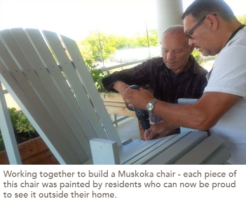 A resident and a staff member work together to put together a Muskoka chair