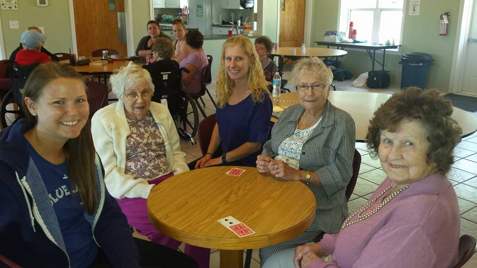 Staff and residents sit at a table in the lodge playing cards, smiling.