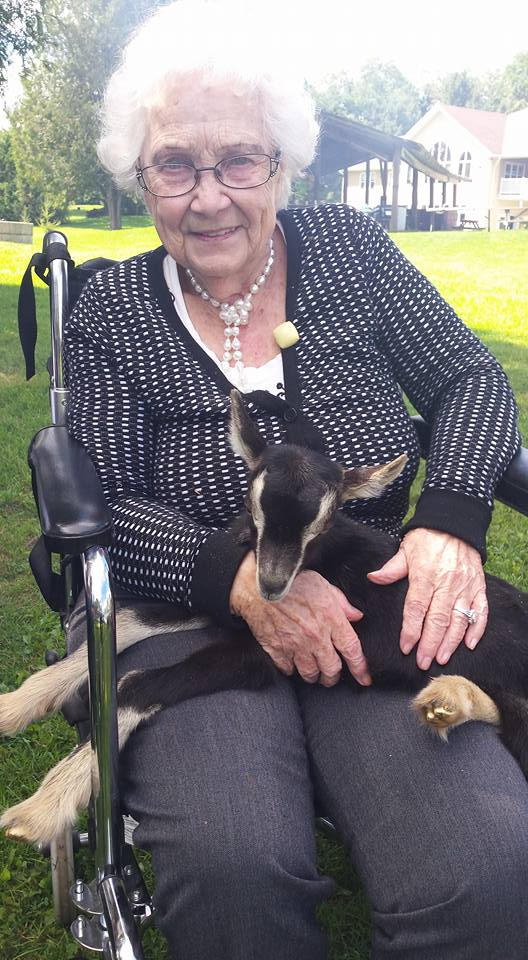 Resident Pearl sits outdoors in her wheelchair with a baby goat in her lap, smiling