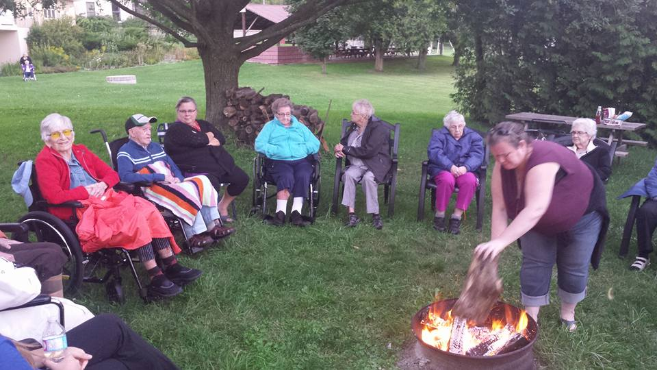 A group of residents and staff sit outside in a circle while one of the staff tend to a campfire in the center