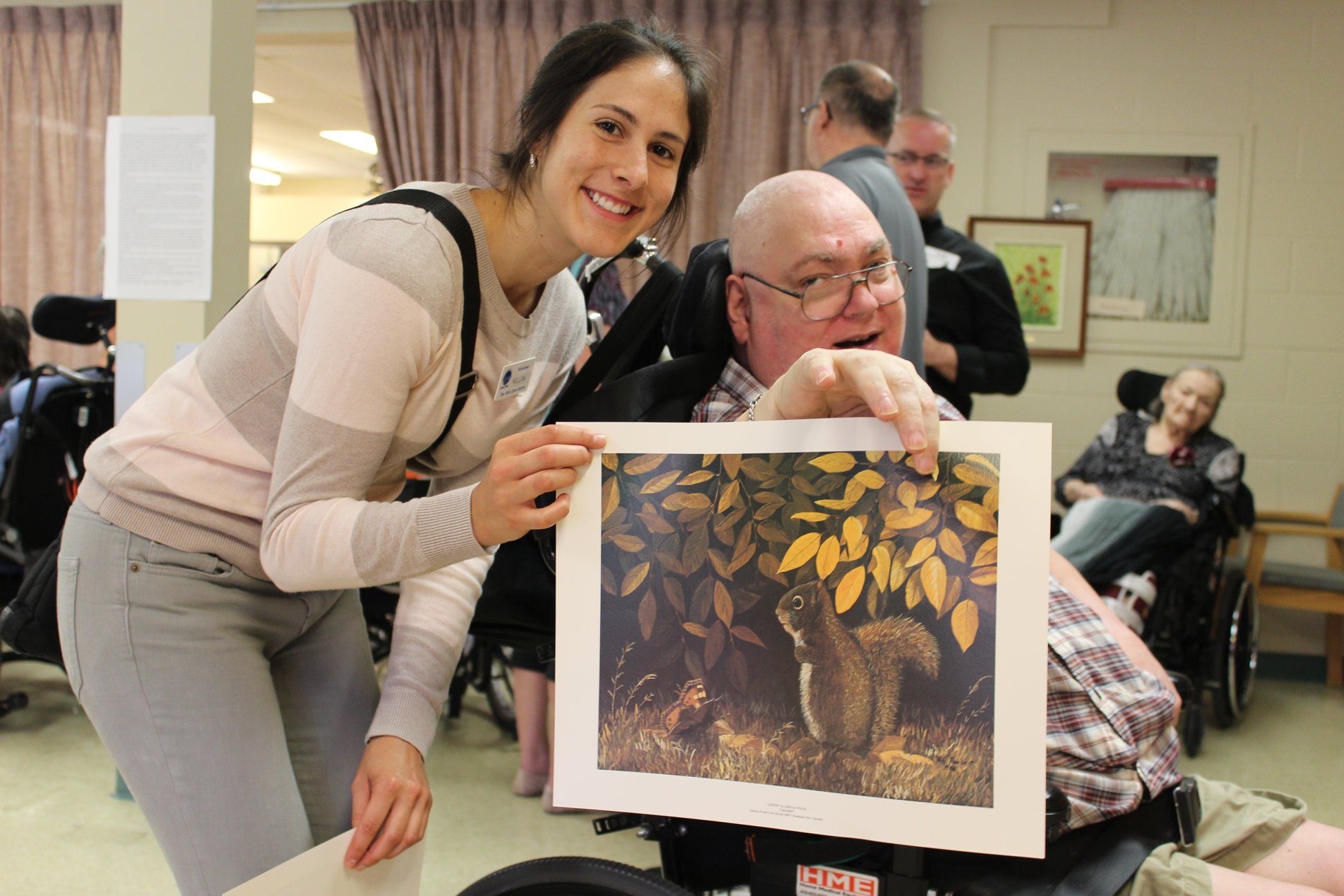 A man sits in a wheelchair holding a painting with a young woman smiling beside him