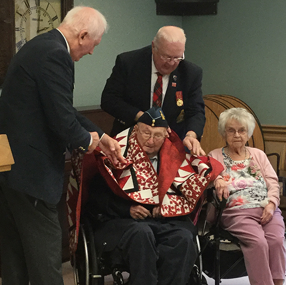 Arthur gets draped with the quit by two representatives from Quilts of Valour Canada