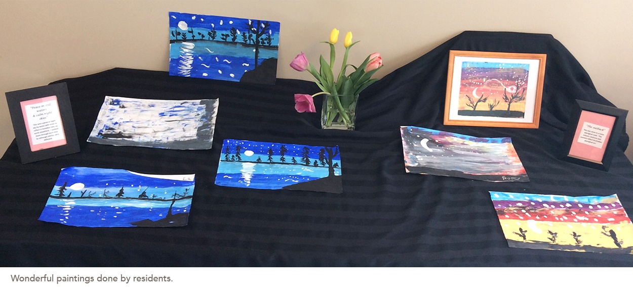 A number of painting done by residents are on display on a table
