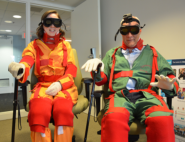 A woman and man sit in chairs dressed in special suits the simulate aging
