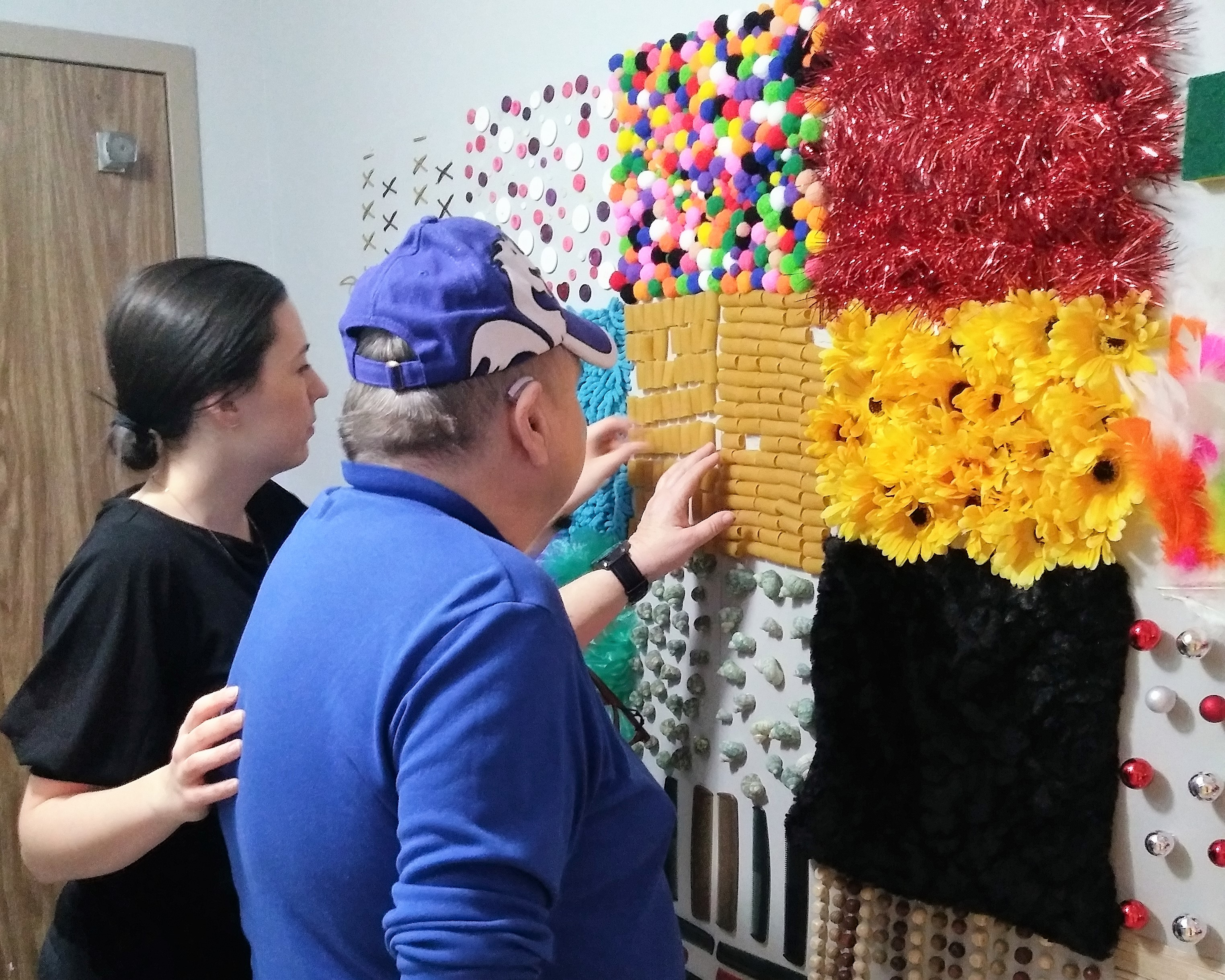 BSO team lead Samantha and resident Lynda take part in a sensory activity, touching raised objects on the wall