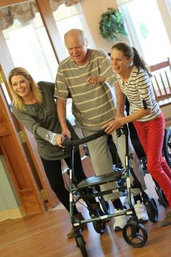 Resident Carl Woodworth walks using a walker and assistance from PSWs Jen and Mandi
