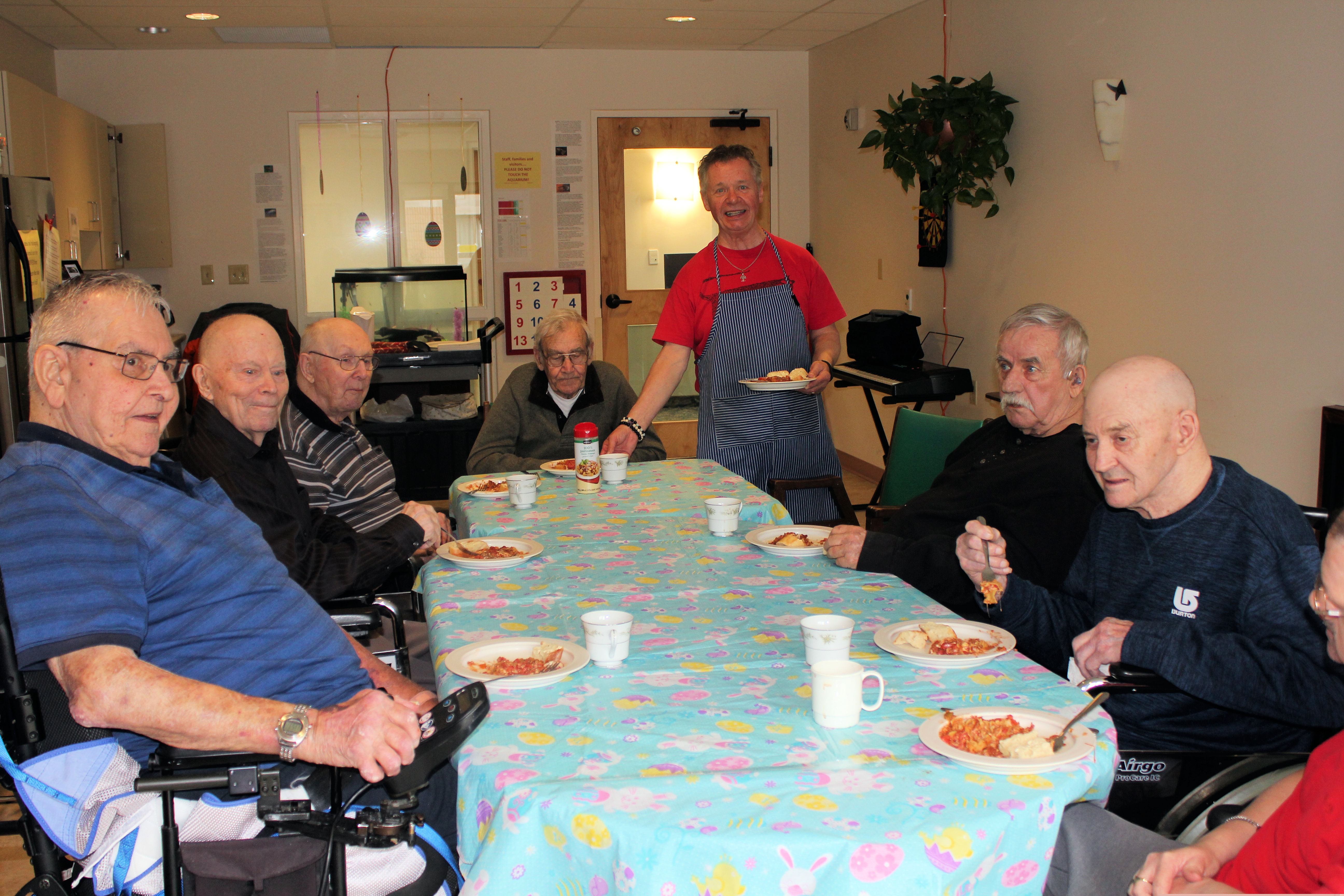 A group of male residents sit around a table while Ray serves them lunch and coffee
