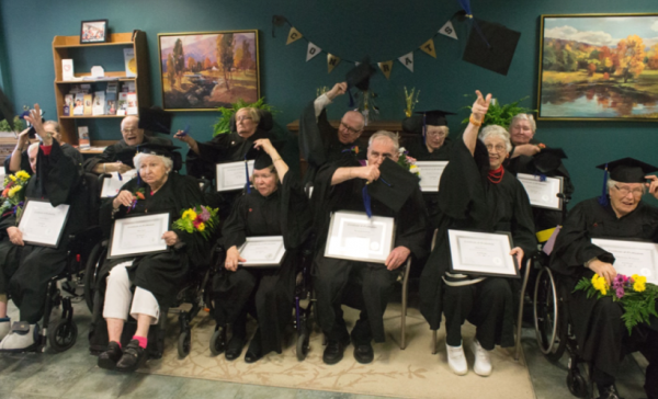 12 residents sit in chairs or wheelchairs in full cap and gowns, holding graduation certificates