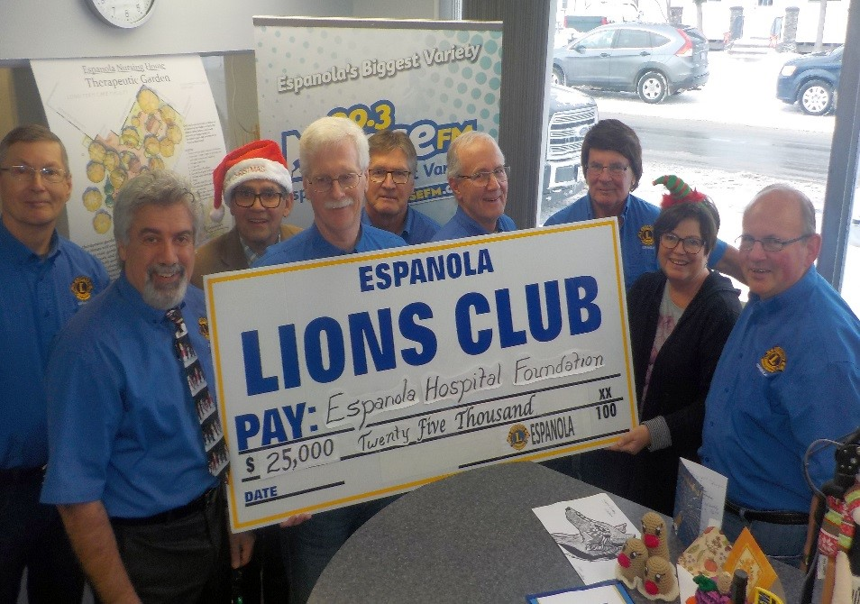 Members of the Espanola Lions Club stand holding a giant cheque for $25,000