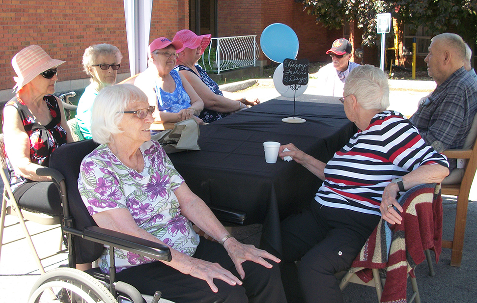 residents sit at a table chatting and enjoying the entertainment