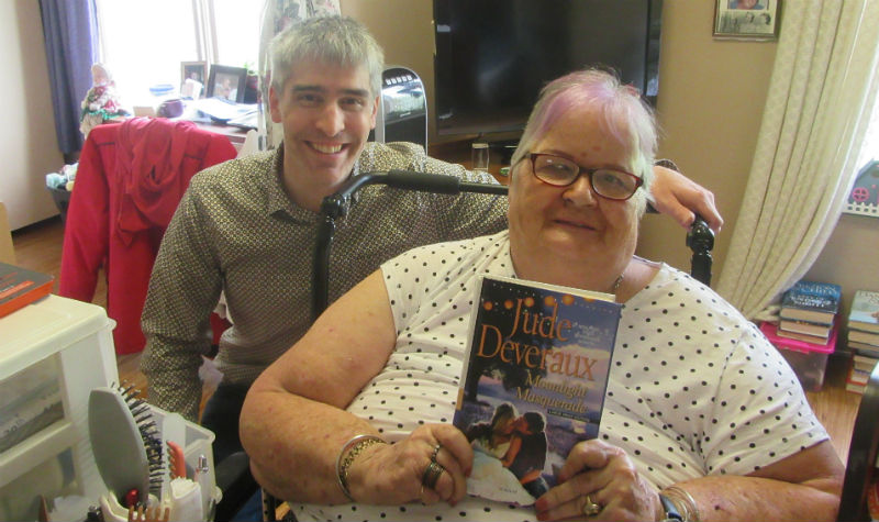 A woman resident holds up a Jude Deveraux book while Gregor smiles beside her