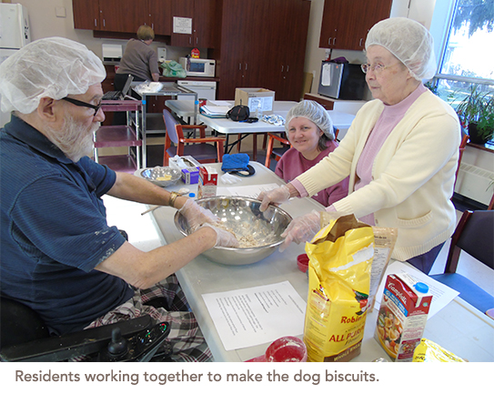 Residents are in the kitchen mixing together ingredients to make dog biscuits
