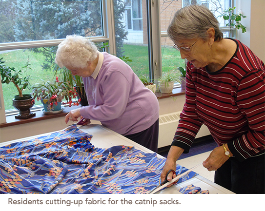 Two residents cut up fabric that will be used to hold the catnip