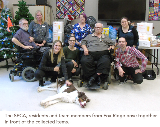 A group of residents gather along with SPCA staff and a dog, and all their collected items