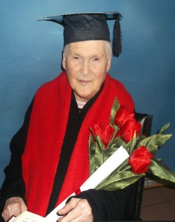 Georgina at the home's graduation, holding flowers and wearing a cap and gown