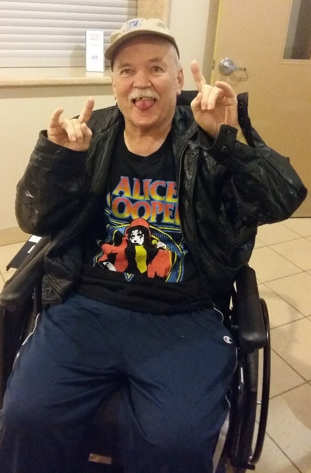 Keith sits in his wheelchair signaling a 'rock on' pose with his hands, wearing an Alice Cooper shirt