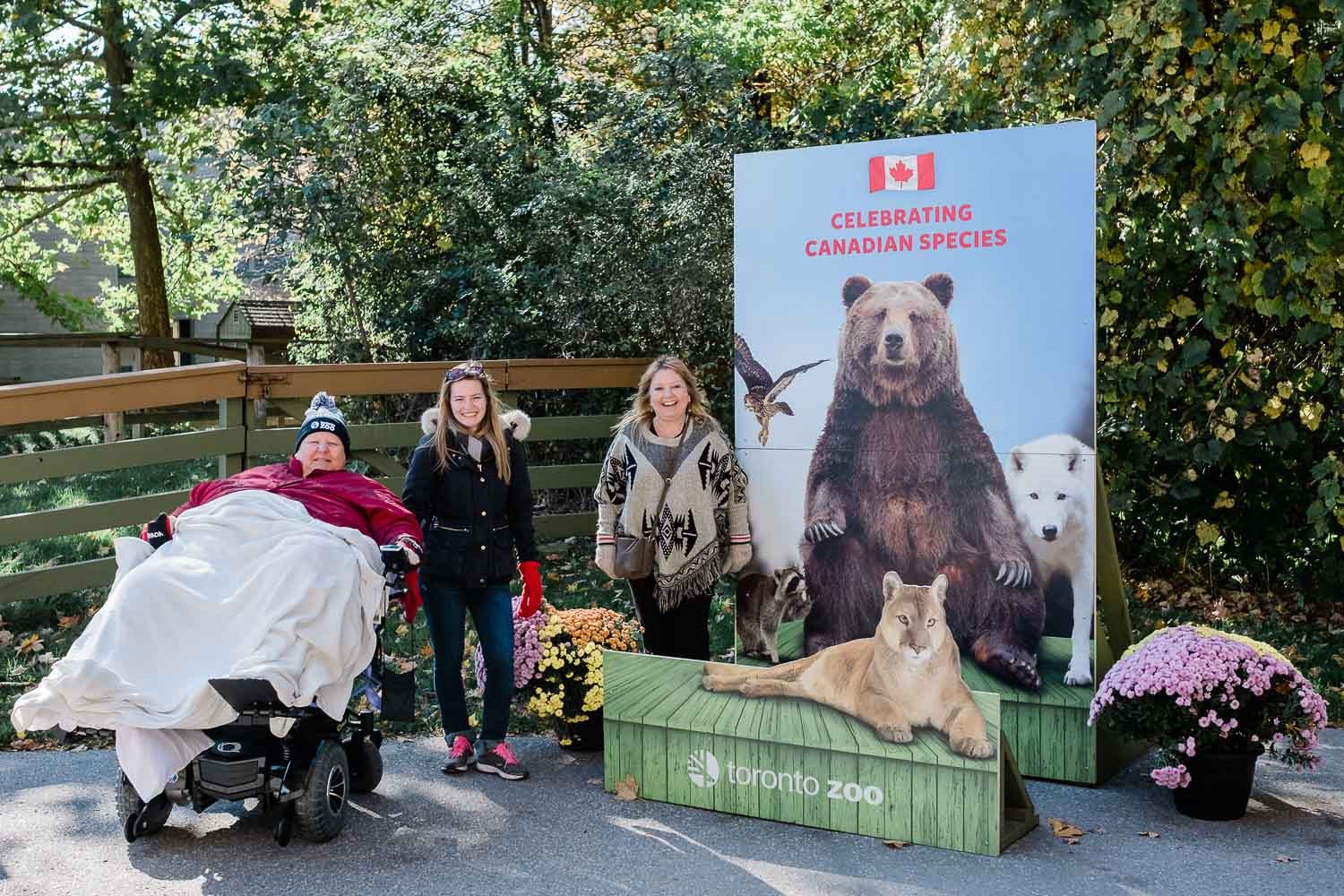Lorraine and two staff members pose in front of a bear sign at the Zoo