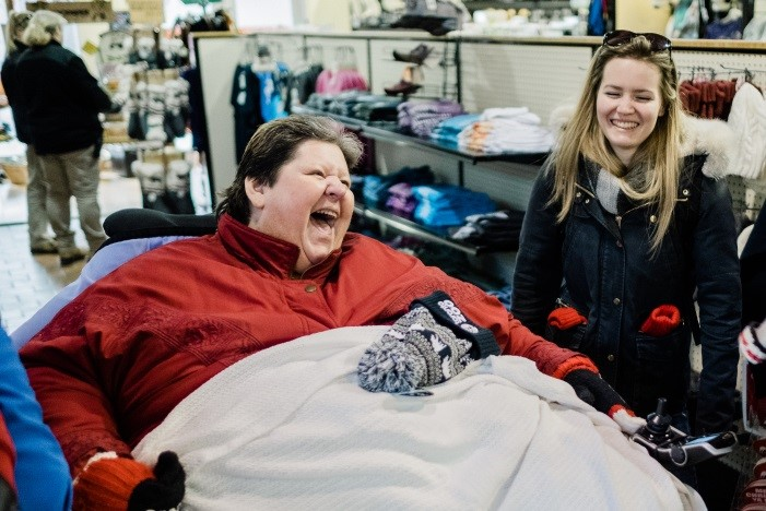 Lorraine smiles in the gift shop with a staff member by her side