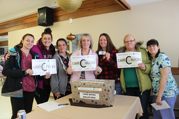 "seven women gather holding up signs that say ""care bucks"" in front of a bin"
