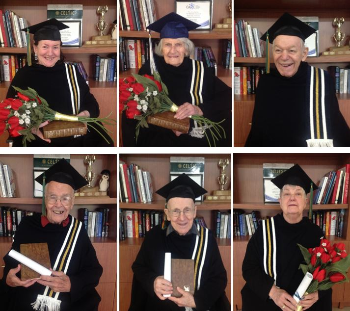6 residents pose in caps and gowns, holding diplomas