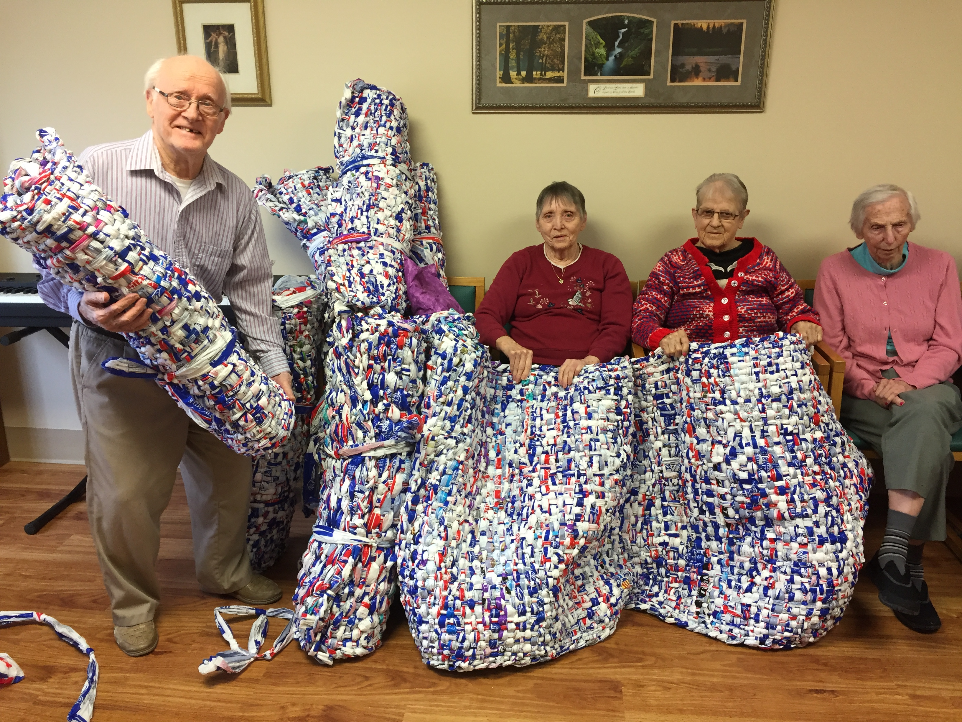 residents hold up mats made of milk bags