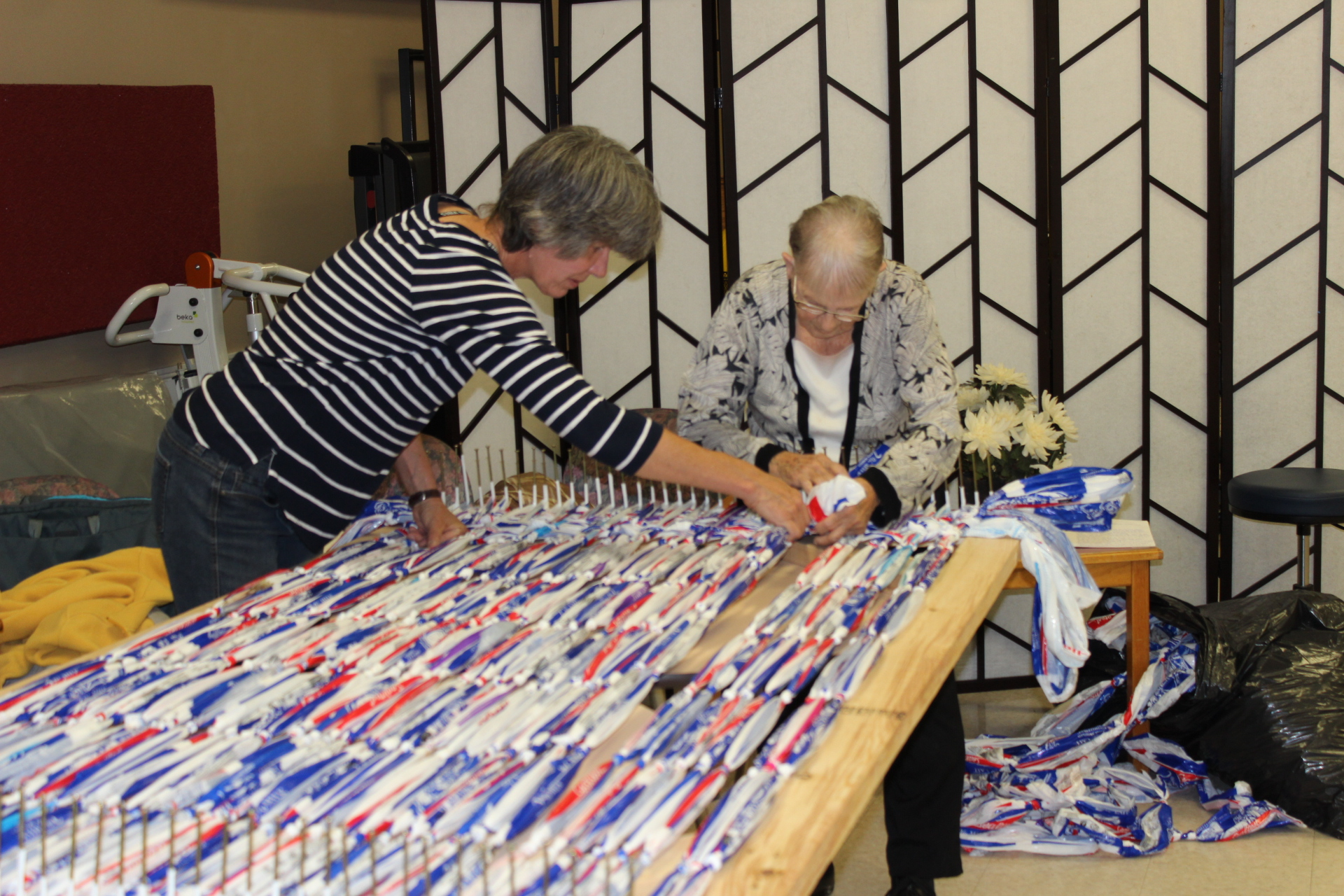 a staff member helps a resident make a milk bag mat