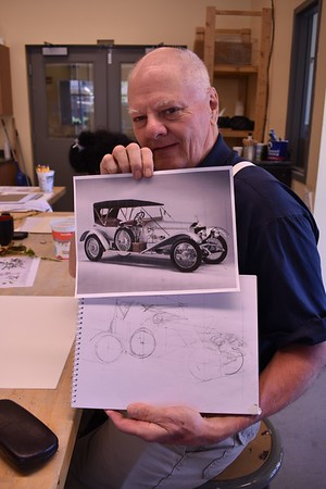 Ron holds up sketch against the original before he paints it