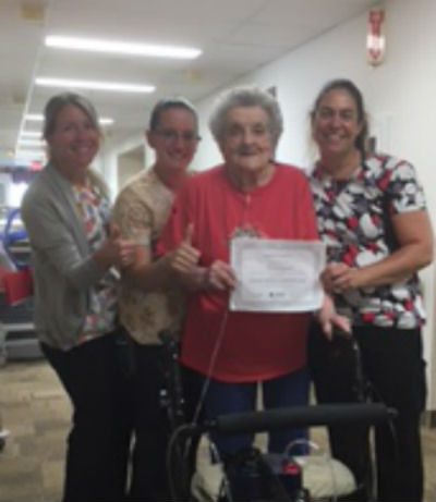 3 nurses stand with resident Rosina, who holds her rehab certificate up smiling