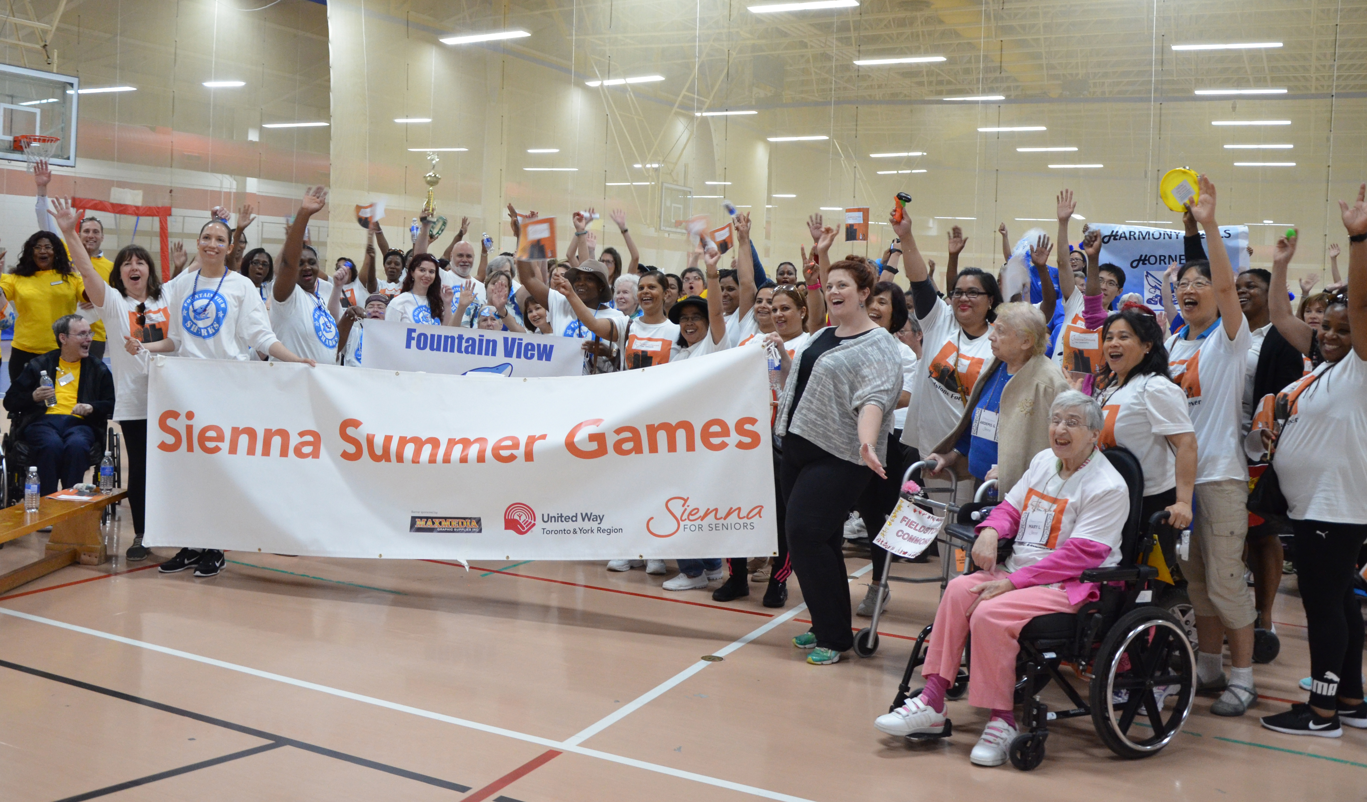 A large group of people, including long-term care residents, staff, and community members are gathered in a gym, holding a large sign that says 'Sienna Summer Games.'
