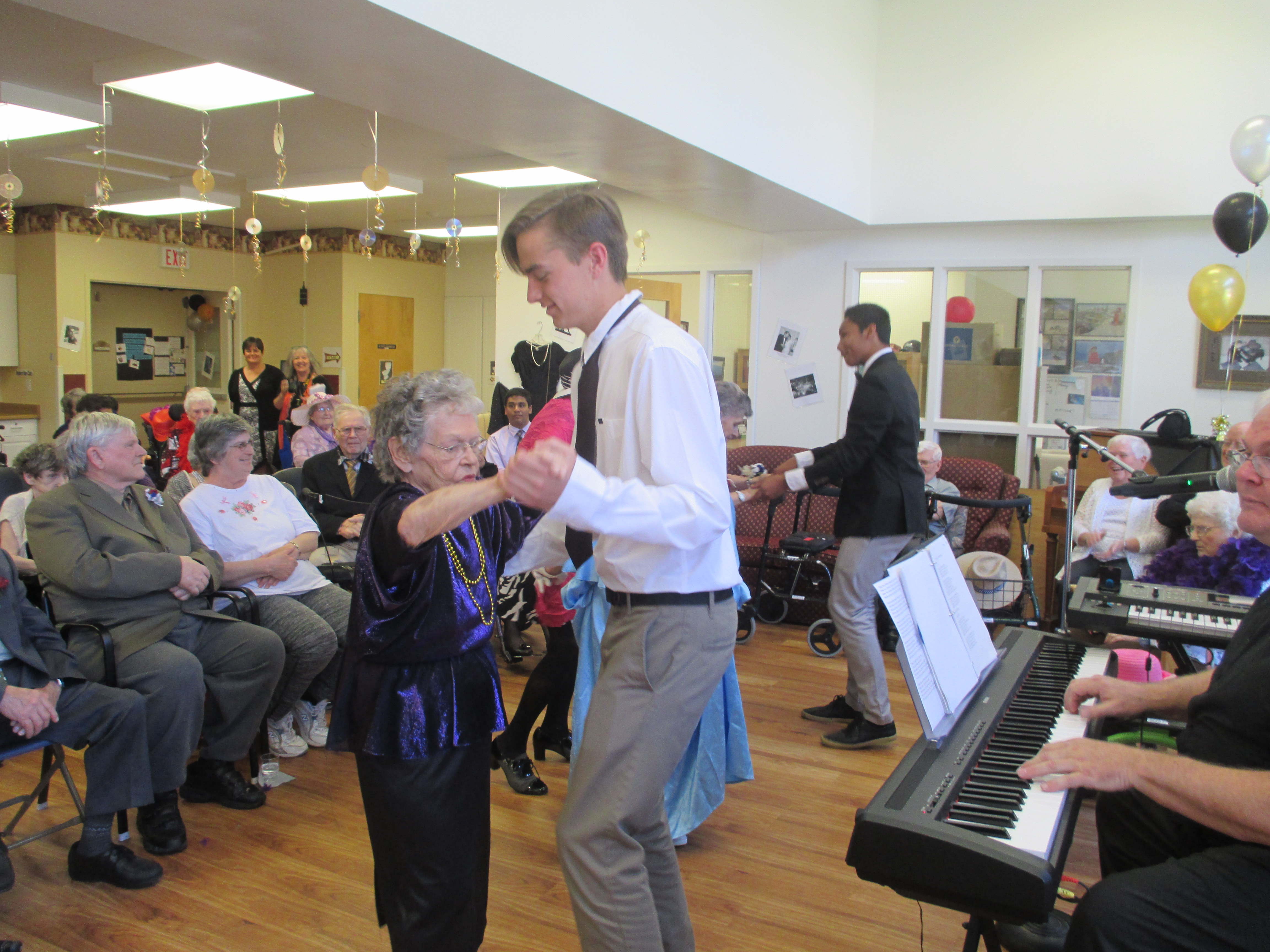 Southampton Care Centre resident Audrey W dances with one of the high school students at her 'Senior Prom,' while other residents look on and enjoy the music